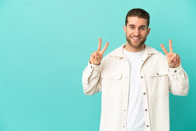 Knappe blonde man over geïsoleerde blauwe achtergrond met overwinningsteken met beide handen showing