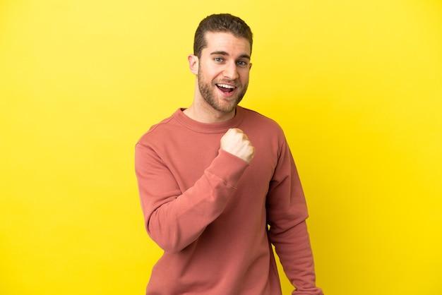 Knappe blonde man over geïsoleerde gele achtergrond die een overwinning viert