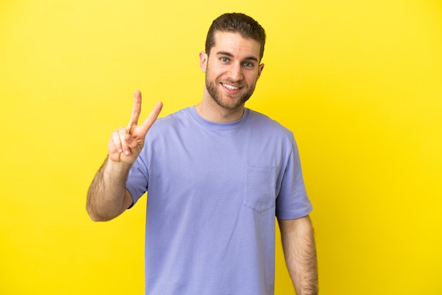 Knappe blonde man over geïsoleerde gele achtergrond glimlachend en overwinningsteken tonen