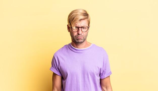 Knappe blonde volwassen man die er gek en grappig uitziet met een dwaze schele uitdrukking, grapjes maakt en voor de gek houdt