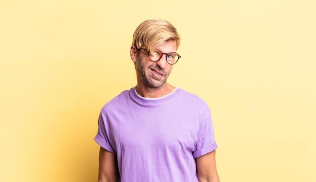 Knappe blonde volwassen man die er gelukkig en vriendelijk uitziet, lacht en je met een positieve houding aankijkt
