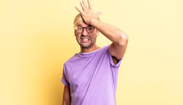 Knappe blonde volwassen man die handpalm naar voorhoofd steekt en denkt oeps, na een domme fout te hebben gemaakt of zich te herinneren, zich dom te voelen