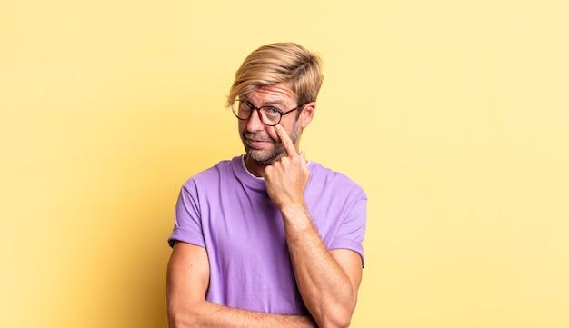 Knappe blonde volwassen man die je in de gaten houdt, niet vertrouwt, kijkt en alert en waakzaam blijft
