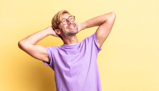 Knappe blonde volwassen man die lacht en zich ontspannen, tevreden en zorgeloos voelt, positief lacht en chillt