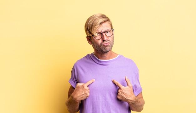 Knappe blonde volwassen man die naar zichzelf wijst met een verwarde en vragende blik, geschokt en verrast om gekozen te worden