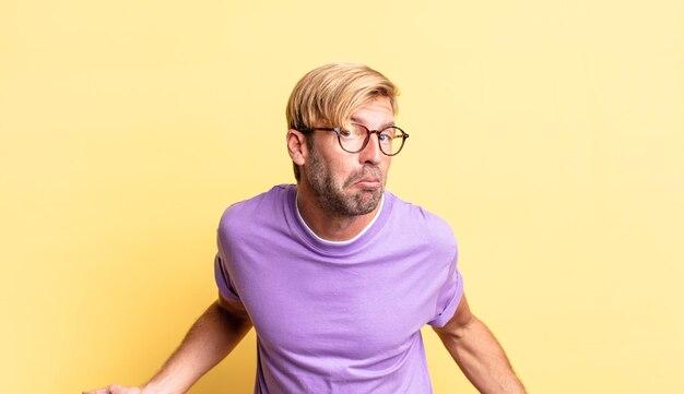 Knappe blonde volwassen man die zich geen idee en verward voelt, geen idee heeft, absoluut verbaasd met een domme of dwaze blik