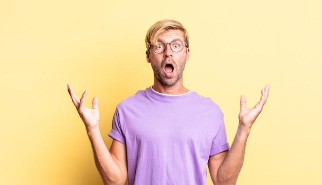 Knappe blonde volwassen man die zich gelukkig, opgewonden, verrast of geschokt voelt, glimlachend en verbaasd over iets ongelooflijks