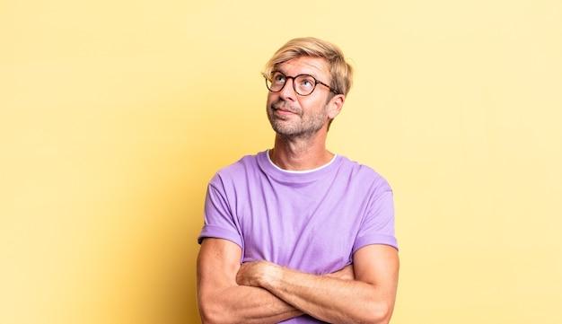 Knappe blonde volwassen man die zich gelukkig, trots en hoopvol voelt, zich afvraagt of denkt, omhoog kijkt om ruimte te kopiëren met gekruiste armen
