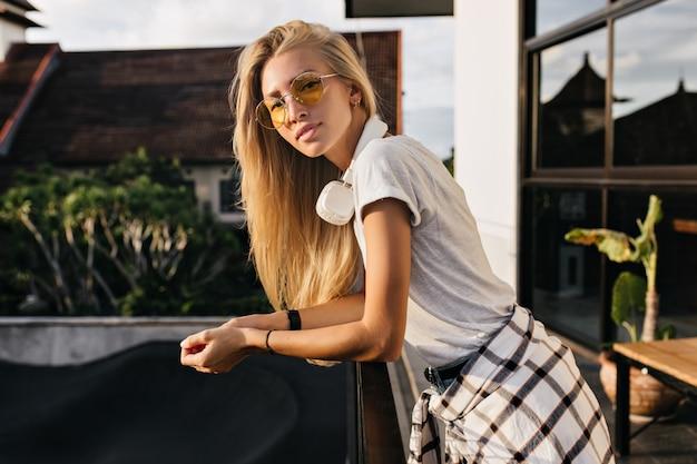 Knappe blonde vrouw in trendy kleding poseren met geïnteresseerde gezichtsuitdrukking in zomerdag.