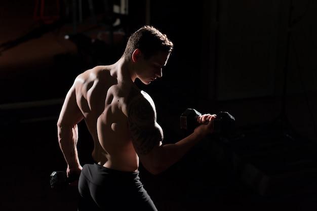 Knappe bodybuilder die van de machts de atletische kerel oefeningen met domoor doen