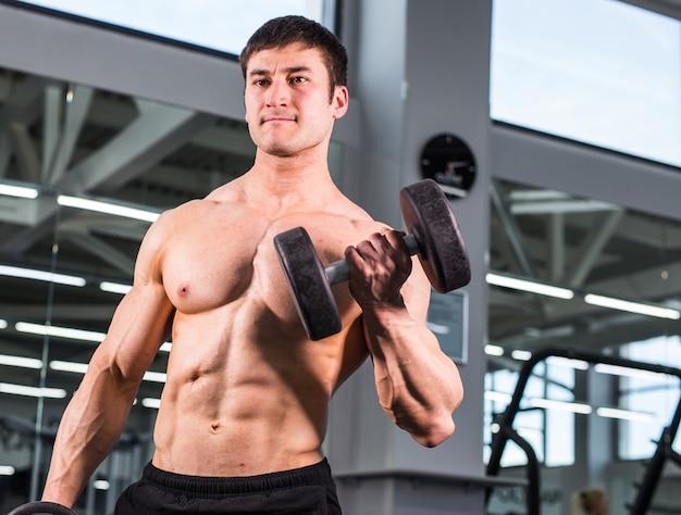 Knappe bodybuilder man met grote spieren in de sportschool