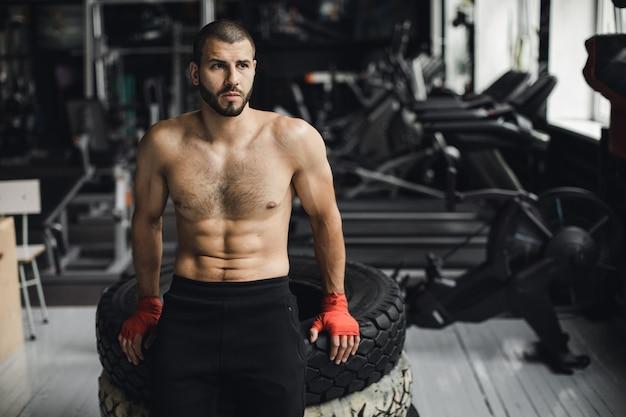 Knappe bodybuilder met gesloten ogen rust na het doen van voorhamer oefeningen in de sportschool. zijaanzichtfoto van volledige lengte. hoge kwaliteit foto