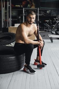 Knappe bodybuilder met gesloten ogen rust na het doen van voorhameroefeningen op de foto van het zijaanzicht van de volledige lengte van de sportschool