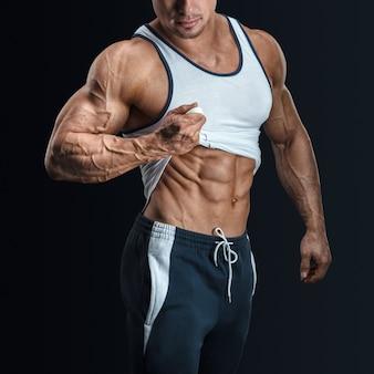 Knappe bodybuilder toont zijn geweldige lichaamsbouw en trekt tanktop omhoog om gespierde buikspieren te onthullen