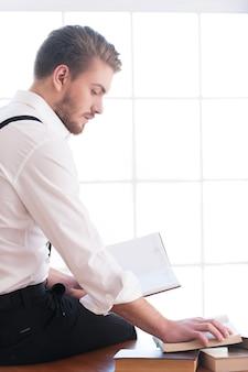Knappe boekenwurm. achteraanzicht van een bedachtzame jongeman in hemd en bretels die op tafel zit en een boek leest dat erop ligt