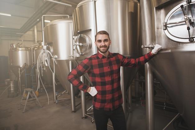 Knappe brouwer die vers gebrouwen bier in zijn bierfabriek onderzoekt