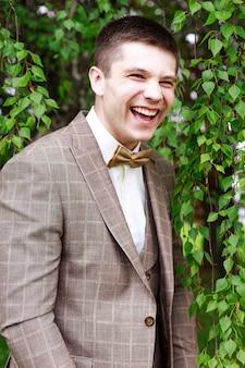 Knappe bruidegom bij huwelijkstuxedo die en op bruid glimlacht wachten. gelukkig lachend bruidegom pasgetrouwde. rijke bruidegom op huwelijksdag. elegante bruidegom in smokingkostuum. knappe blanke man in smoking.