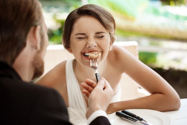 Knappe bruidegom die zijn bruid met croissant in koffie voeden.