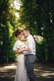 Knappe bruidegom die zijn mooie overweldigende bruid met boeket in romantisch europees park koesteren