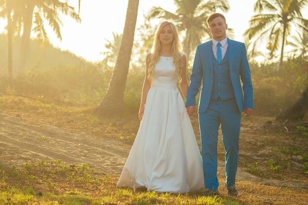 Knappe bruidegom in een chique pak en een charmante bruid in een mooie trouwjurk die lacht op de achtergrond van palmbomen. concept van een chique en rijke huwelijksceremonie op het strand