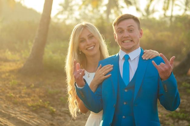 Knappe bruidegom in een chique pak en een mooie bruid in een mooie trouwjurk die grimassen trekt en plezier heeft tegen de achtergrond van palmbomen. concept van een chique en rijke huwelijksceremonie op het strand
