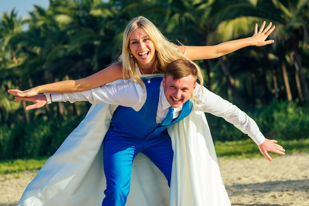 Knappe bruidegom in een chique pak en een mooie bruid in een trouwjurk hebben plezier en grimassen op het strand. concept van een chique en rijke huwelijksceremonie op het strand.