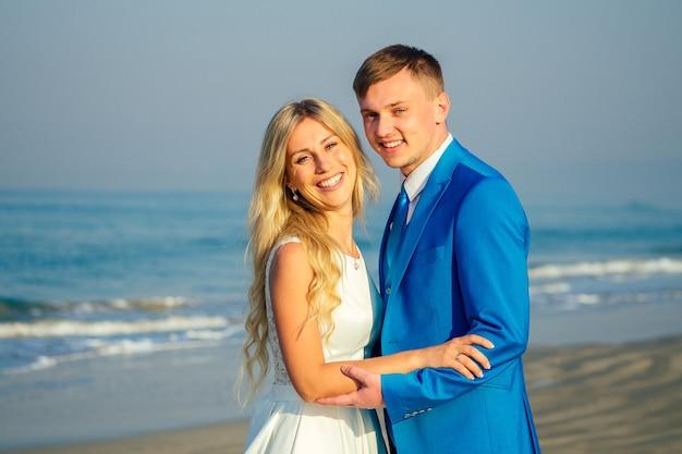 Knappe bruidegom in een chique pak en een mooie bruid in een trouwjurk knuffelen en houden van elkaar op het strand. concept van een chique en rijke huwelijksceremonie op het strand