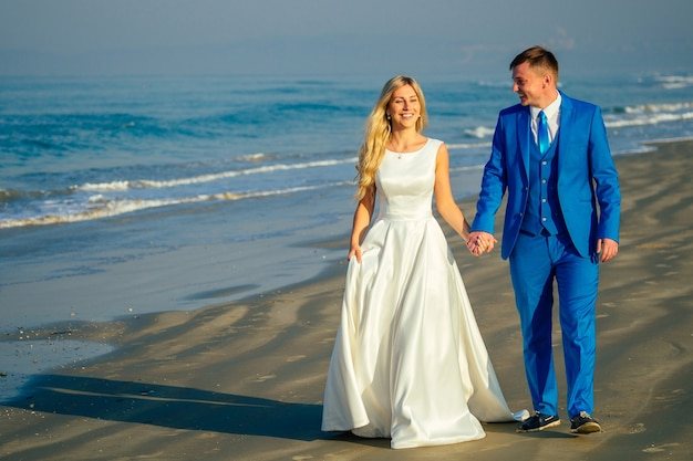 Knappe bruidegom in een chique pak en een mooie bruid in een trouwjurk lopen langs het strand. concept van een chique en rijke huwelijksceremonie op het strand