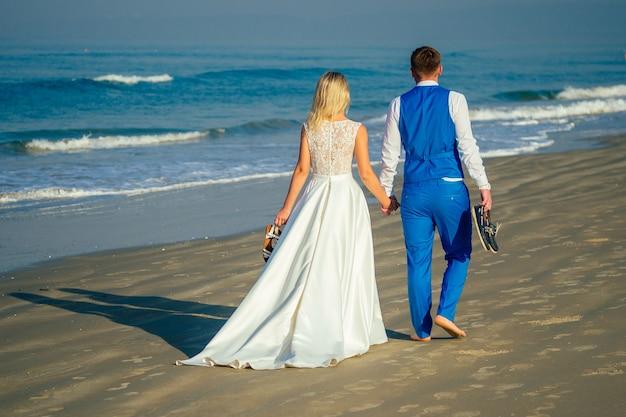 Knappe bruidegom in een chique pak en een mooie bruid in een trouwjurk lopen op het strand (uitzicht vanaf de achterkant). concept van een chique en rijke huwelijksceremonie op het strand