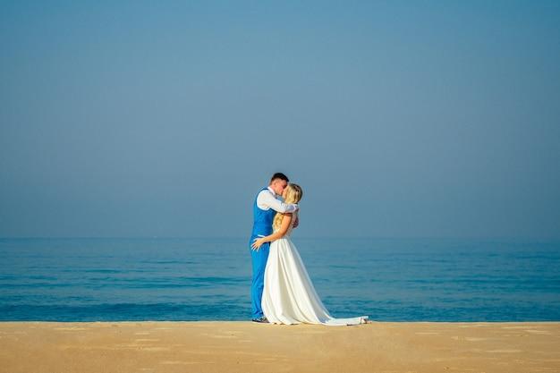 Knappe bruidegom in een chique pak en een mooie bruid in een trouwjurk op het strand. concept van een chique en rijke huwelijksceremonie op het strand. kopieerruimte