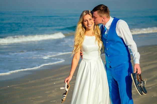 Knappe bruidegom in een chique pak kussen een mooie bruid in een trouwjurk op het strand. concept van een chique en rijke huwelijksceremonie op het strand