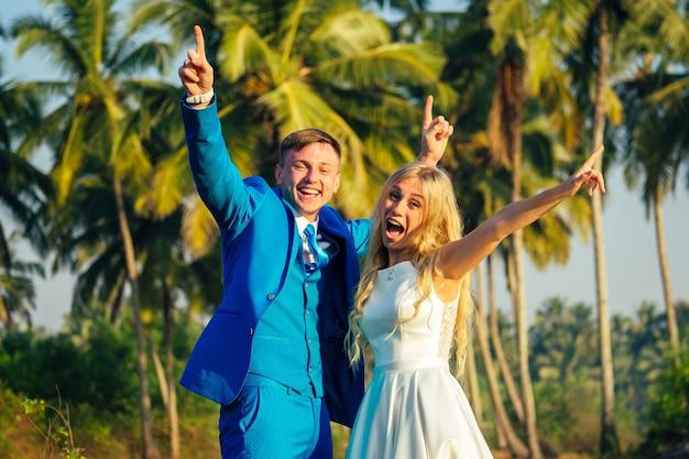 Knappe bruidegom in een luxe pak en een mooie bruid in een mooie trouwjurk glimlachend en poseren op een achtergrond van palmbomen. concept van een chique en rijke huwelijksceremonie op het strand