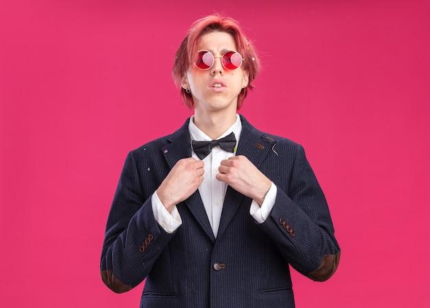 Knappe bruidegom in pak met vlinderdas en bril met serieuze zelfverzekerde uitdrukking op roze