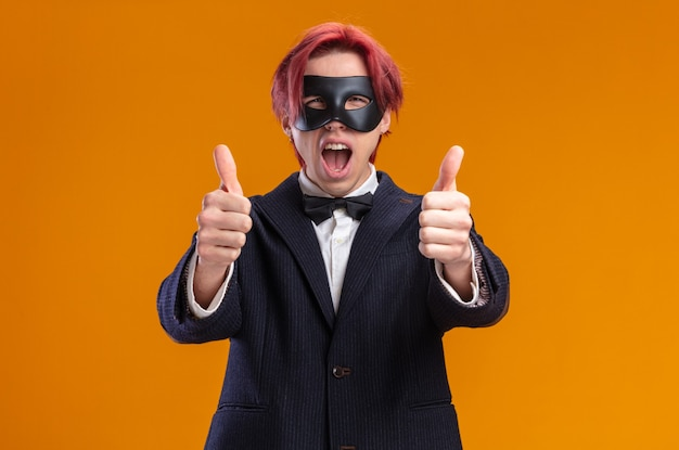 Knappe bruidegom in pak met vlinderdas en maskerademasker glimlachend vrolijk duimen omhoog staand over oranje muur