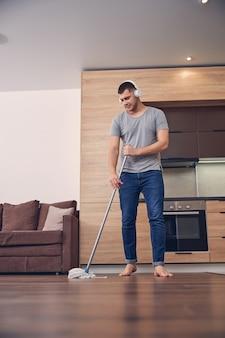 Knappe brunette man in koptelefoon wassen van de vloer met dweilstok en luisteren naar muziek