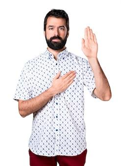 Knappe brunette man met baard die een eed maakt
