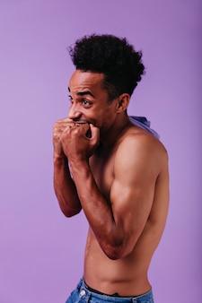 Knappe brunette man zonder t-shirt geluk uitdrukken. binnenfoto van vrolijke zwarte man geïsoleerd op pastel paarse muur.