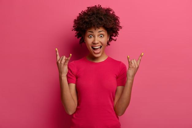 Knappe brutale vrouw toont rock n roll-gebaar, heeft plezier, luistert naar favoriete muziek, roept met vreugde, heeft emotionele expressie, draagt een casual t-shirt, geïsoleerd op een roze muur. zwaar metalen bord