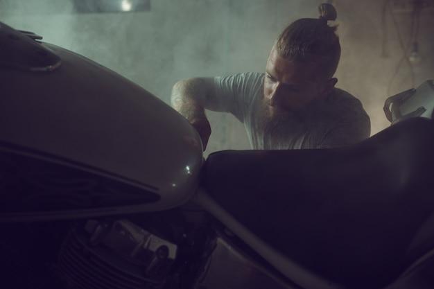 Knappe brute man met een baard repareren van een motorfiets in zijn garage