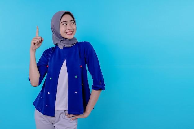 Knappe charismatische jonge vrouw met het dragen van hijab die omhoog wijst geïsoleerd op lichtblauwe achtergrond
