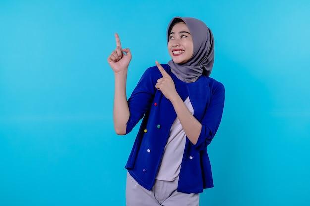 Knappe charismatische jonge vrouw met het dragen van hijab wijzend geïsoleerd op lichtblauwe achtergrond
