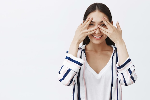 Knappe, charmante en vriendelijke jonge vrouw in gestreepte blouse, die de ogen bedekt met de handpalmen en door de vingers gluurt, breed glimlachend