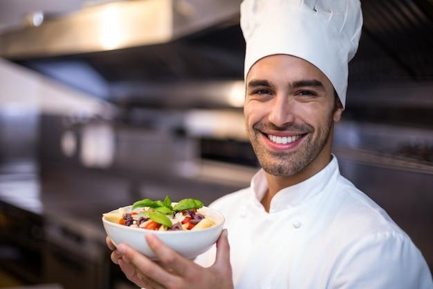 Knappe chef-kok die deegwaren voorstelt