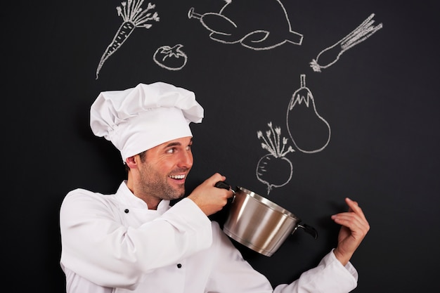 Knappe chef-kok die ingrediënten voor soep vangt