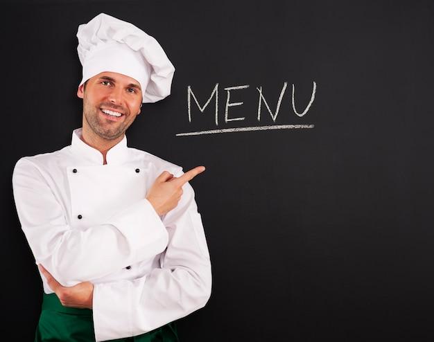 Knappe chef-kok die menu toont
