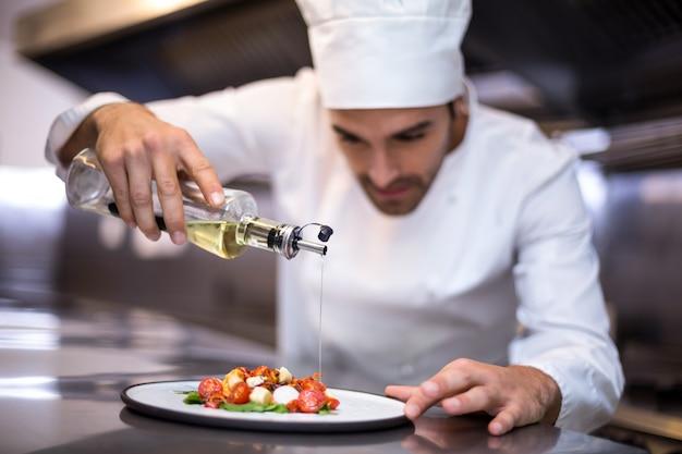 Knappe chef-kok gietende olijfolie op maaltijd