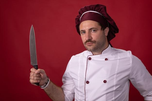Knappe chef-kok vormt met mes in zijn hand