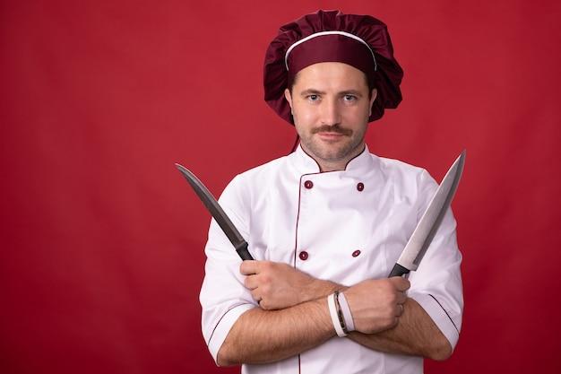 Knappe chef-kok vormt met messen in zijn handen