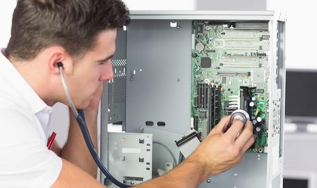 Knappe computeringenieur die hardware met stethoscoop onderzoeken