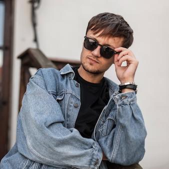 Knappe coole jongeman hipster met modieuze zwarte zonnebril